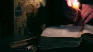 stock-footage-reading-old-books-by-candlelight-bible